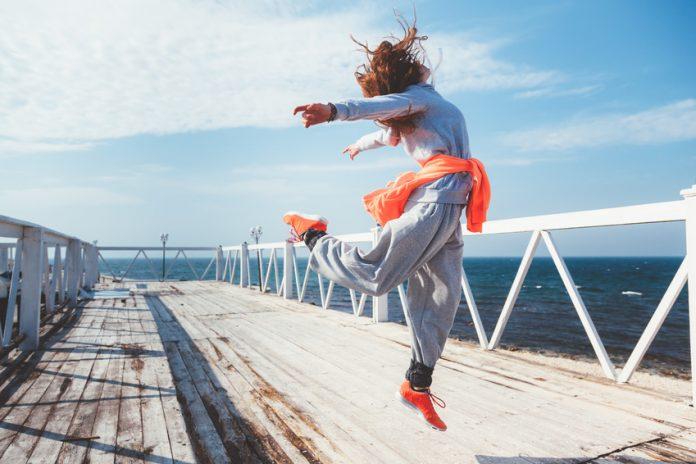 Frau springt vor Freude in die Luft - sie ist am Meer, sie ist in Bewegung!