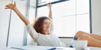 Frau am Schreibtisch wirft die Arme vor Freude in die Luft und legt die Füsse hoch: öfter mal unter dem Arbeiten am Computer abschalten